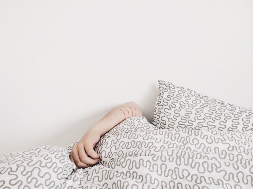 One arm poking out from under a duvet