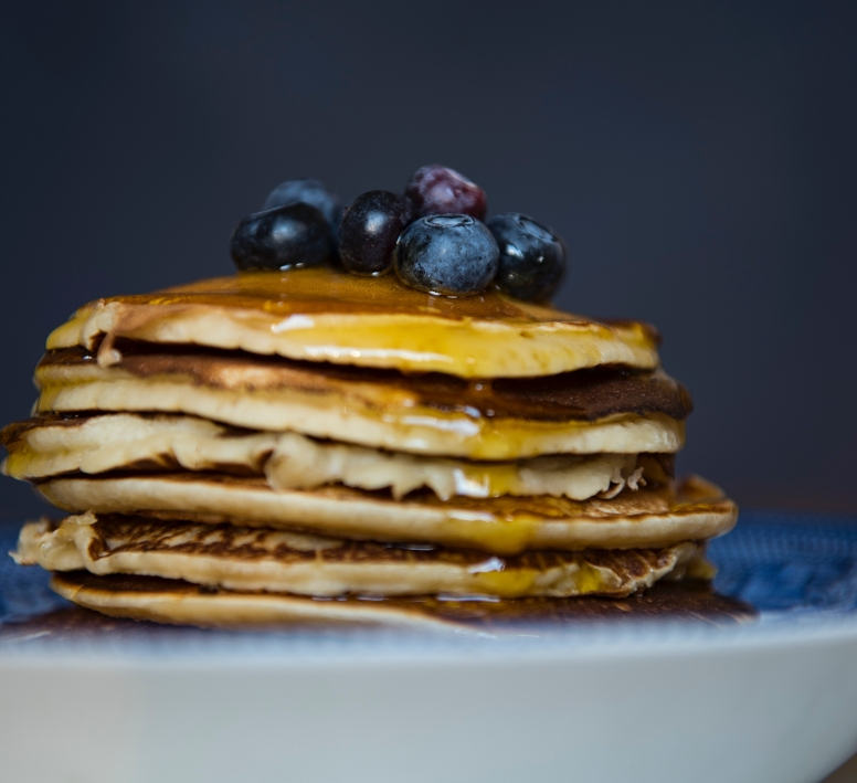 Stack of pancakes with blueberries and maple syrup